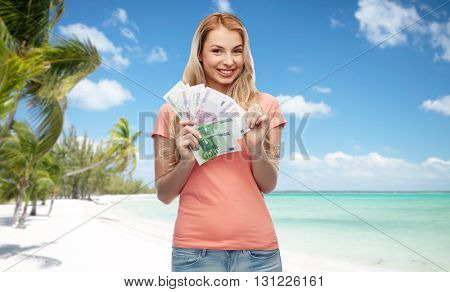 money, finances, travel, tourism and people concept - happy young woman with euro cash money over exotic tropical beach with palm trees background