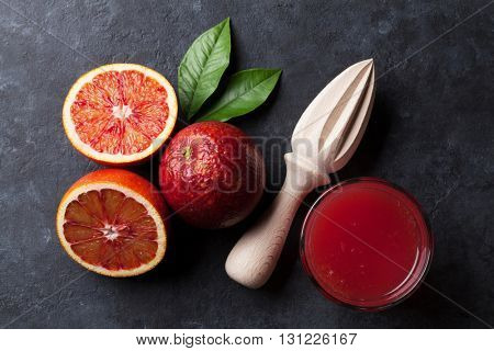 Red oranges and juice glass on stone background. Top view