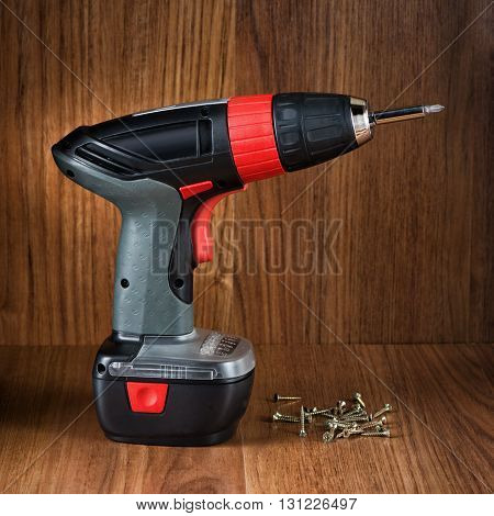 The electric tool for twisting of screws against wooden texture