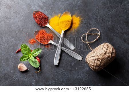 Colorful spices in spoons and mint herb. Top view