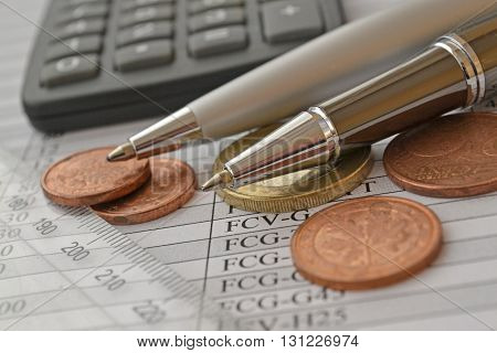 Financial background with money ruler calculator table and pens.