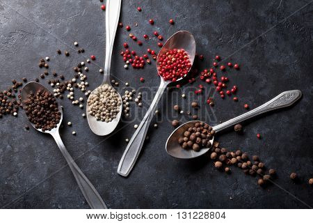Colorful peppercorn. Red, white and black pepper spices in spoons on stone table. Top view
