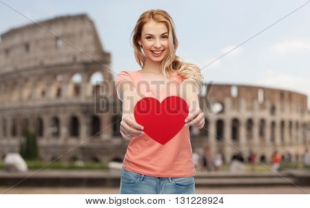 love, travel, tourism, valentines day and people concept - smiling young woman or teenage girl with blank red heart shape over coliseum background