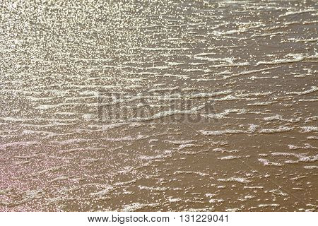 Seafoam bubbles closeup with water edge on a sandy beach.