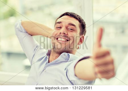 business, people and gesture concept - smiling man showing thumbs up at home or office