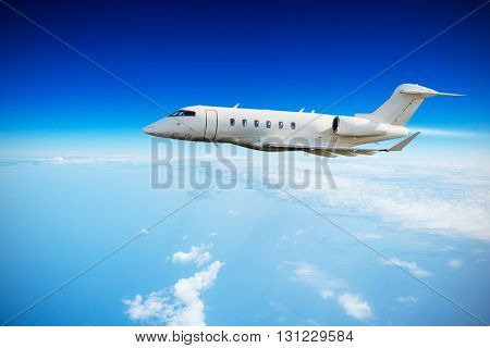 Luxury private jet plane flying above clouds in day light