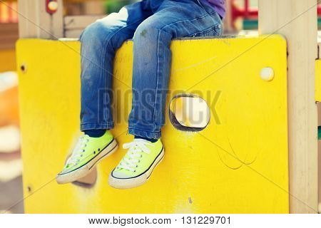 summer, childhood, leisure and people concept - close up of little boy legs sitting on climbing frame at children playground