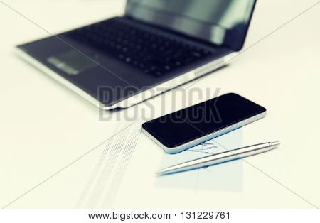 business, technology and statistics concept - close up of smartphone, laptop computer and chart with pen on office table