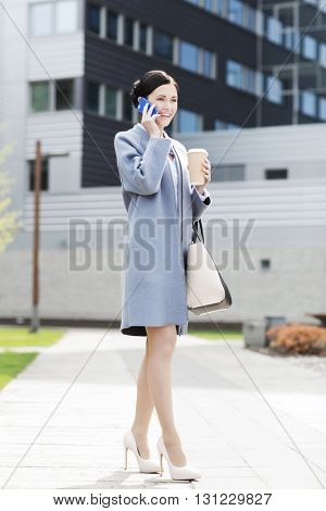 business and people concept - young smiling businesswoman calling on smartphone over office building