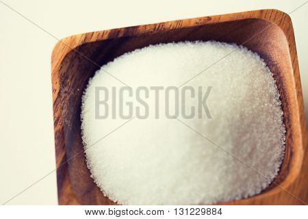 food, junk-food, cooking and unhealthy eating concept - close up of white sugar heap in wooden bowl