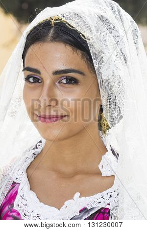 QUARTU S.E., ITALY - September 21, 2014: Parade of Sardinian costumes and floats for the grape festival in honor of the celebration of St. Helena. - Portrait of a beautiful smiling girl in Sardinian costumes