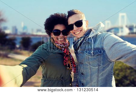 tourism, travel, people, leisure and technology concept - happy international teenage couple taking selfie over rainbow bridge at tokyo in japan background
