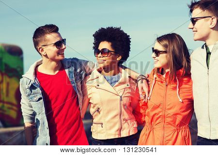 friendship, tourism, travel and people concept - group of happy teenage friends in sunglasses hugging and talking on city street