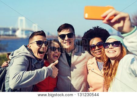 people, travel, tourism, friendship and technology concept - group of happy teenage friends taking selfie with smartphone and showing thumbs up over rainbow bridge at tokyo in japan background