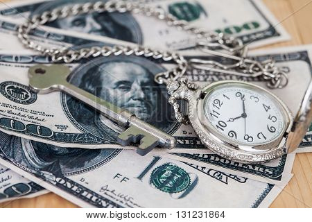 Time and money concept image - old silver pocket watch and US currency .vintage style light and ton