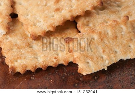 Salted cracker with sesame on a board close up
