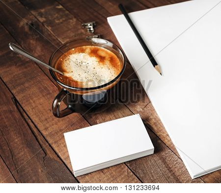 Blank paperwork template on vintage wooden background. Close-up of blank stationery paper letterhead coffee cup and pencil. Mock-up for design portfolios.