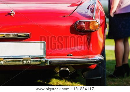 Close-up of the rear of the red vintage car. Back view of retro car. Vintage red car. Detail of a vintage car. Shallow depth of field. Selective focus.
