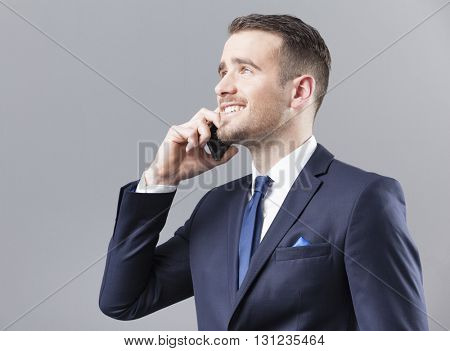 Happy smiling businessman talking on the phone on grey background