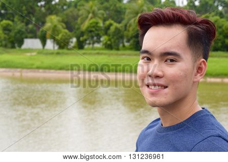 Young asian male with mild acne smiling