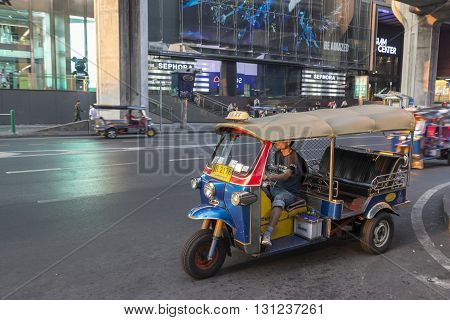 BANGKOK THAILAND - APR 17 : tuktuk is parking on sidewalk of siam square in evening time on april 17 2016 thailand. tuktuk is popular taxi service of tourists in bangkok