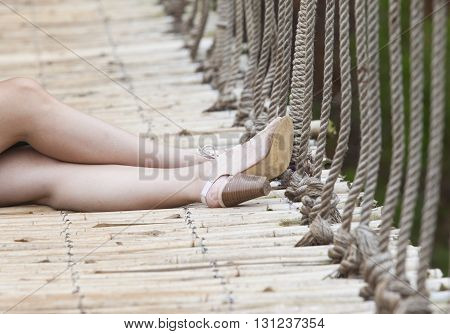 Beautiful her feet with sandals on a suspend bridge