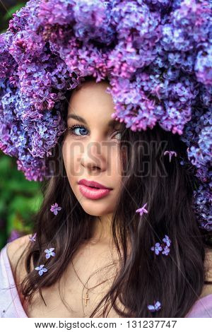 Portrait of a beautiful young girl in a wreath of lilac. Selective focus on the eye.