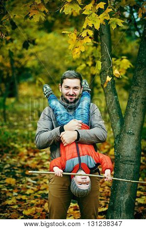 happy father and son playing outdoors in autumn Park