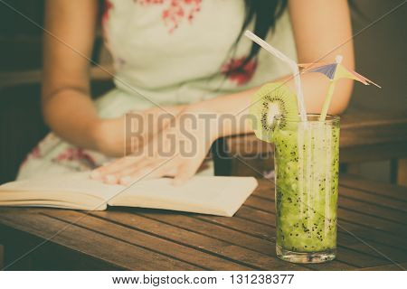Glass of kiwi smoothie and female reading the book in the background