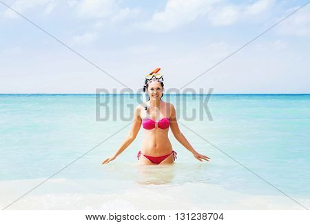 Cheerful young lady with snorkeling mask chilling in the water.