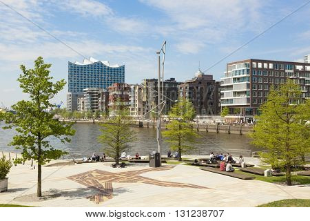 Hamburg, Germany - May 19, 2016: Contemporary architecture at HafenCity quarter with Elbe Philharmonic Hall in background. People relaxing on Marco-Polo-Terrassen square in foreground.