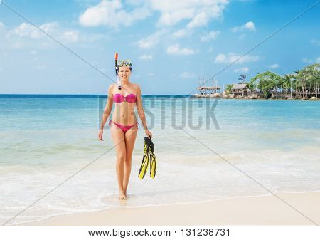 Beautiful, fit, young lady going out from the sea after diving in perfect mood.