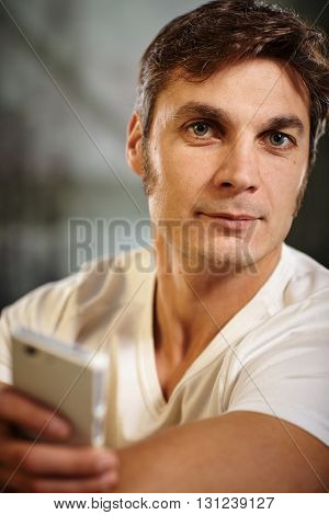 Portrait of man holding mobilephone, looking at camera.