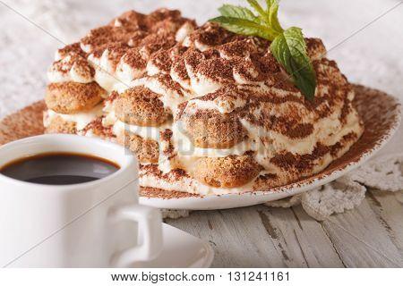 Italian Tiramisu Cake On A Plate And Cup Of Black Coffee Close-up. Horizontal
