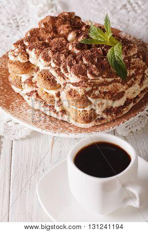 Italian Tiramisu Cake On A Plate And Cup Of Black Coffee Close-up. Vertical