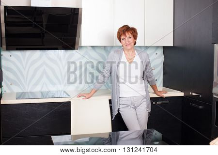 Happy adult woman on kitchen. Mature female at home