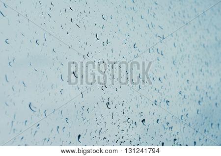 Raindrops on window glass toned blue selective focus tilt shift