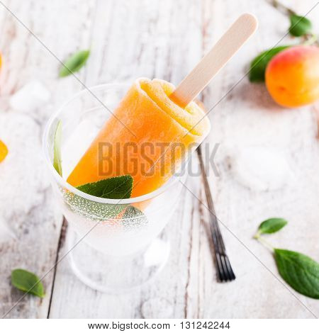 Homemade apricot popsicles in glass with ice and apricot fruits. Summer healty food concept.