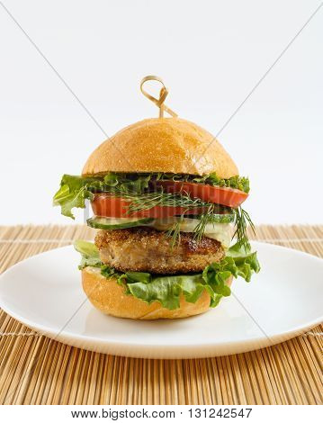 Big beef steak burger with vegetables and herbs on white plate on bamboo placemat against white background close up