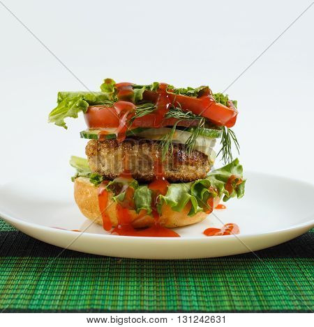 Big beef steak burger with vegetables and herbs on white plate on green bamboo placemat against white background close up