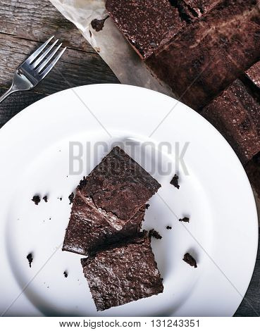 White plate with fresh chocolate brownies on vintage wood background and extra brownies on the pan behind it. Top view.