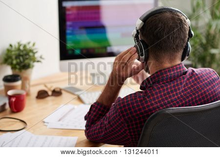 Rear view of sound engineer listening to new music track on computer