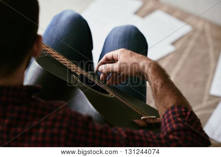 guy playing guitar at home, view from above