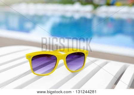 Yellow sunglasses on a lounger by the pool. Close-up.