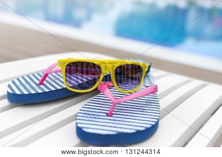 Sunglasses and slates on a poolside lounger.