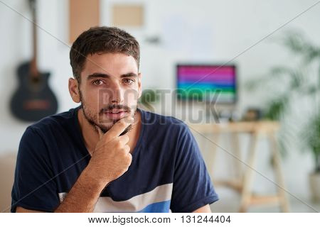 Portrait of handsome pensive musician looking at camera