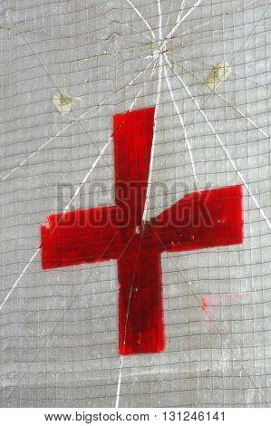 Medical red cross detail old glass door.