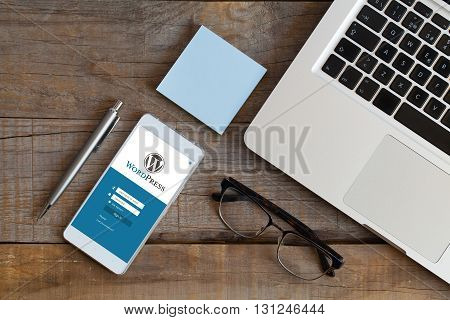 Malaga, Spain - October 29, 2015: Wordpress log in website app in a mobile phone screen, over a wooden workplace. WordPress is a free and open-source blogging tool and a content management system (CMS).