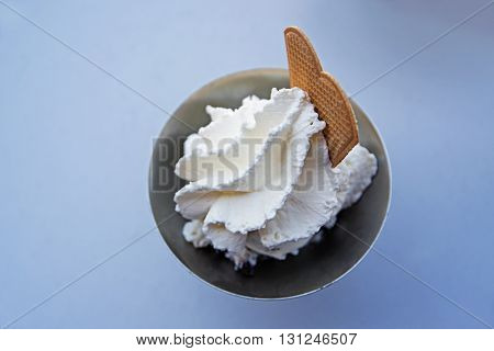 whipped cream and a biscuit over barely visible ice cream in a metallic cup on a light blue background view from above reduced to the essential and nearly a abstract illustration selected focus narrow depth of field