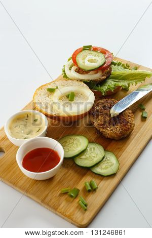 Cooking process of a sandwich burger ingredients on wooden cutting board on wooden table against white background fresh vegetables herbs fried meat buns sauces and knife shallow DOF